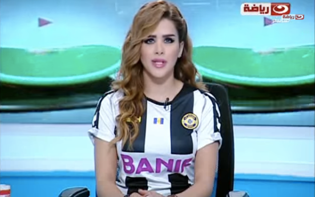 Hot female reporter reads the news wearing a football jersey (video)